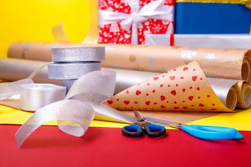 Spostamento di regalo, scatole, carta, nastro e forbici sul fondo di colore Accessori dei materiali per i presente Fine in su immagine stock libera da diritti