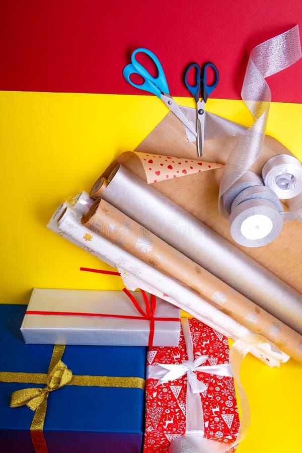 Spostamento di regalo, scatole, carta, nastro e forbici sul fondo di colore Accessori dei materiali per i presente Vista superior fotografia stock