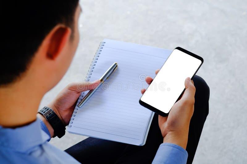 Spot die op smartphone van zakenmanhanden zwarte mobiele telefoon met het lege witte scherm houden royalty-vrije stock afbeeldingen