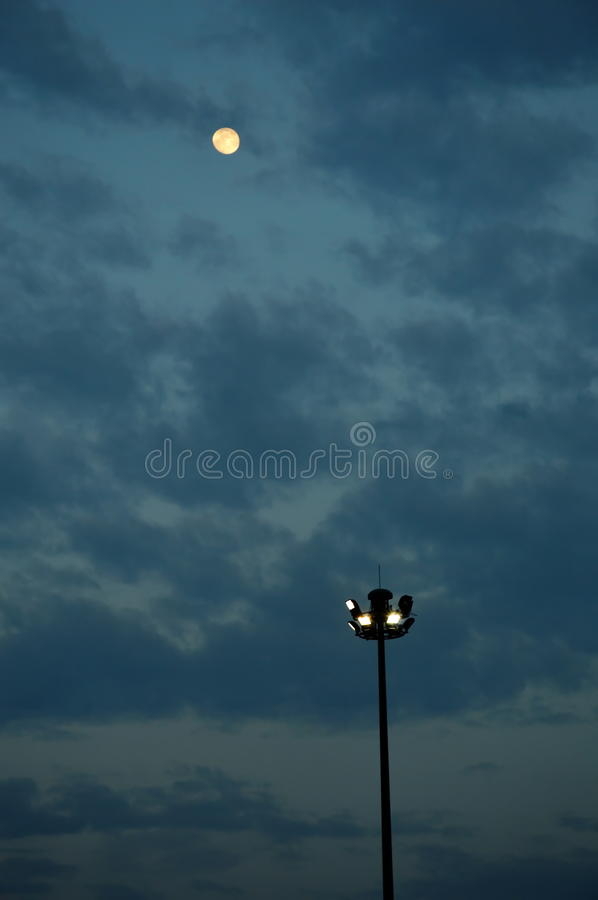 Spot light pole and the moon stock image