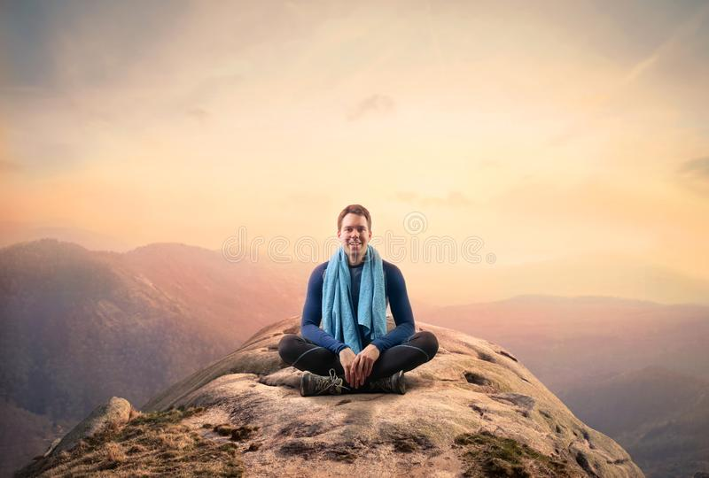 Spot man sitting on a mountain royalty free stock photography