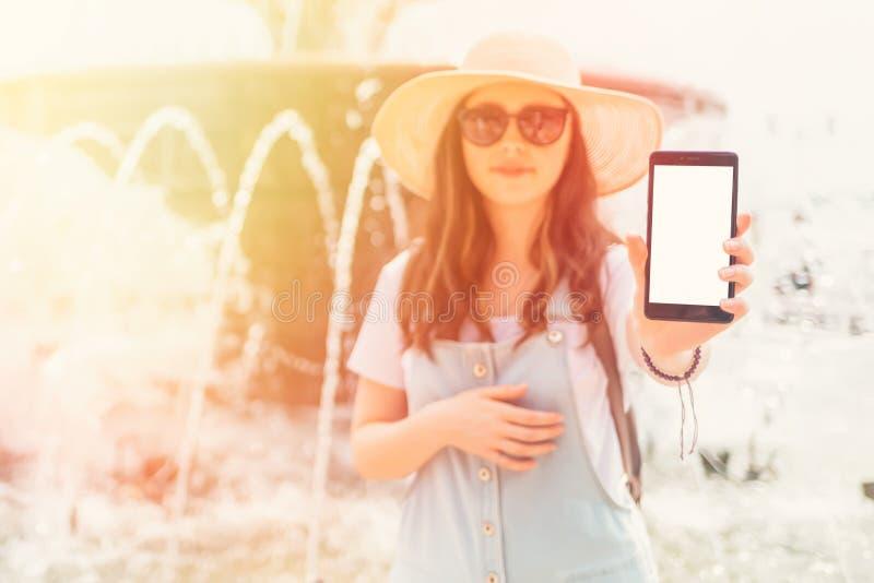 Spot omhoog Mooie jonge vrouw die in een hoed en glazen de telefoon houden isoleer Een fontein op de achtergrond Sluit omhoog stock foto's