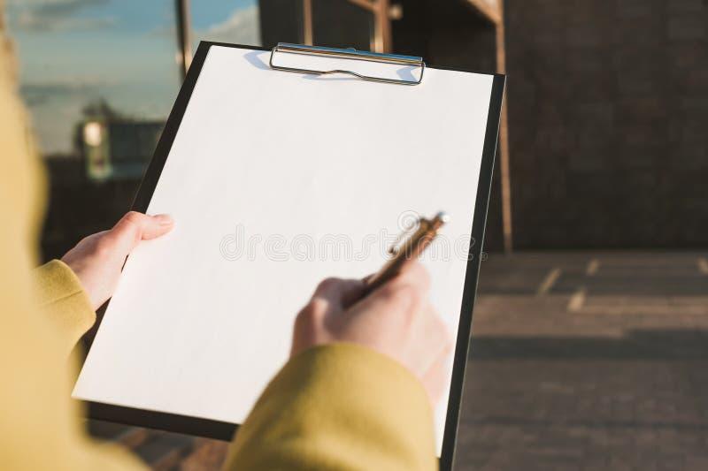 Spot omhoog van de tablet voor het document in de handen van het meisje tegen de achtergrond van het glascentrum stock foto's
