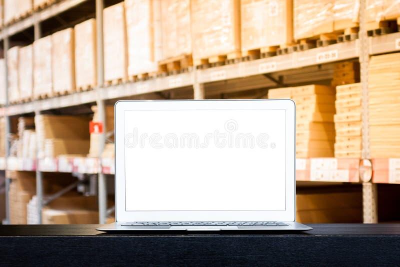 Spot omhoog van moderne computer of laptop met het lege scherm op lijst met Vage vakjes op rijen van planken in pakhuis stock foto