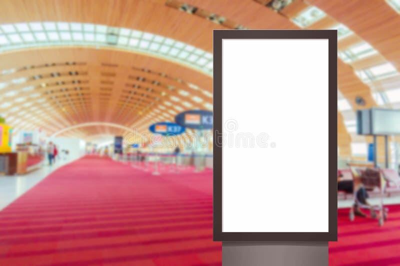 Spot omhoog van verticaal leeg reclameaanplakbord of lichte vakje showcase met mensen die bij luchthaven, exemplaarruimte wachten stock afbeeldingen