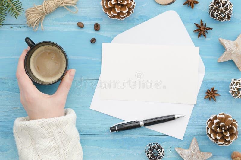 Spot op envelop Vrouwelijke hand die een kop van koffie op vakantiewerkplaats houden met Kerstmisgiften, Nieuwjaardecoratie royalty-vrije stock foto