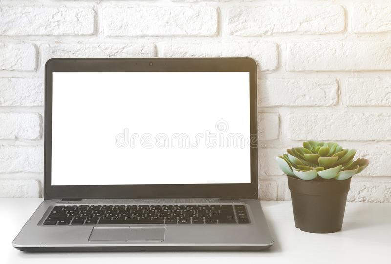 Spot op laptop het computer witte lege scherm op het vooraanzicht van de het werklijst succulente installatie en witte bakstenen  stock foto