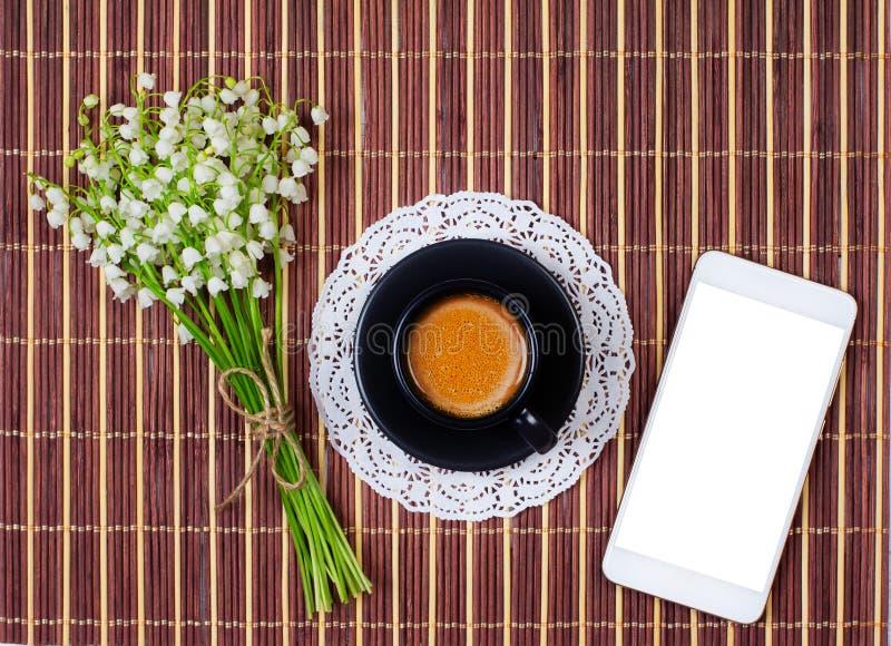 Spot op smartphone, zwarte Kop van koffie met melk op een schotel en een boeket van lelietje-van-dalen op de lijst, hoogste menin stock afbeeldingen