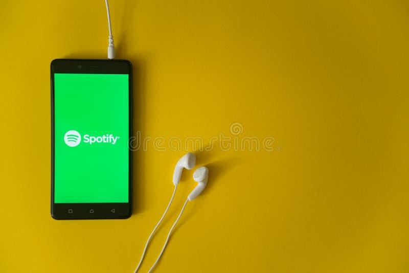 Spotifyembleem op het smartphonescherm op gele achtergrond stock foto's