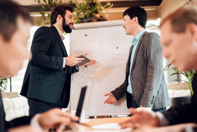 Spotkanie z chińskimi biznesmenami w biurze Mężczyzna dyskutują punkty w dokumentach zdjęcie stock