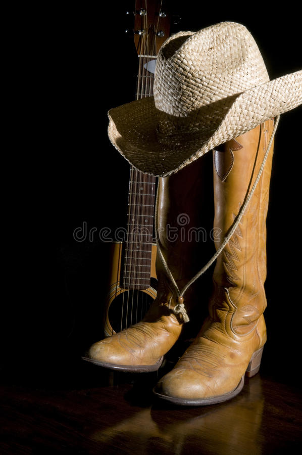 Country Music Spotlight. Spotlight on country music symbols, cowboy boots, acoustic guitar and hat royalty free stock image