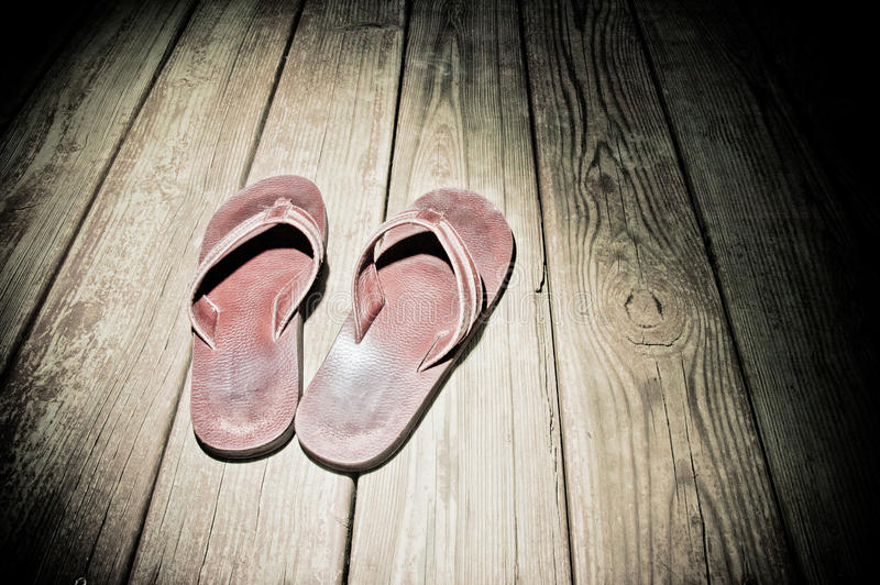 Spotlight Shoes. Spotlight on leather flip flops on wood boards stock photos
