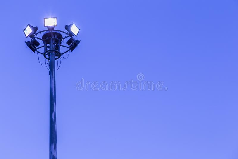 Spotlights tower high voltage in sport stadium on blue sky background.  royalty free stock photos