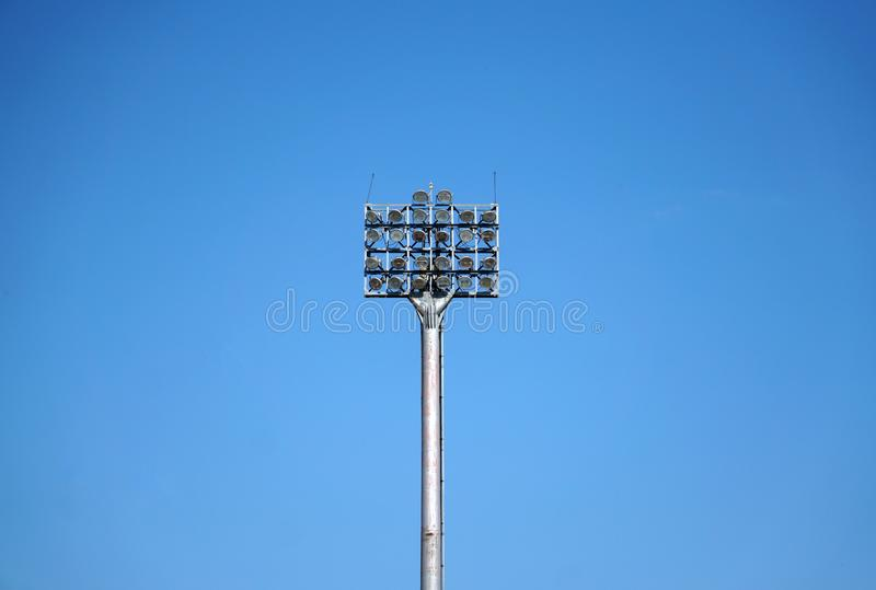 Spotlights tower with a metal pole for the sports arena. Installed around football stadium. Blue sky background. Spotlights tower with a metal pole for the royalty free stock images