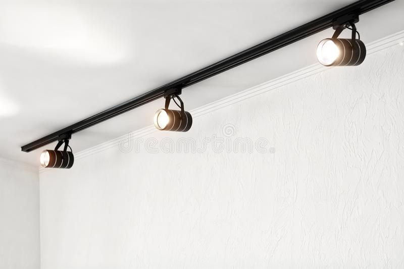 Spotlights under the ceiling on the wall. Track LED-lighting system royalty free stock image