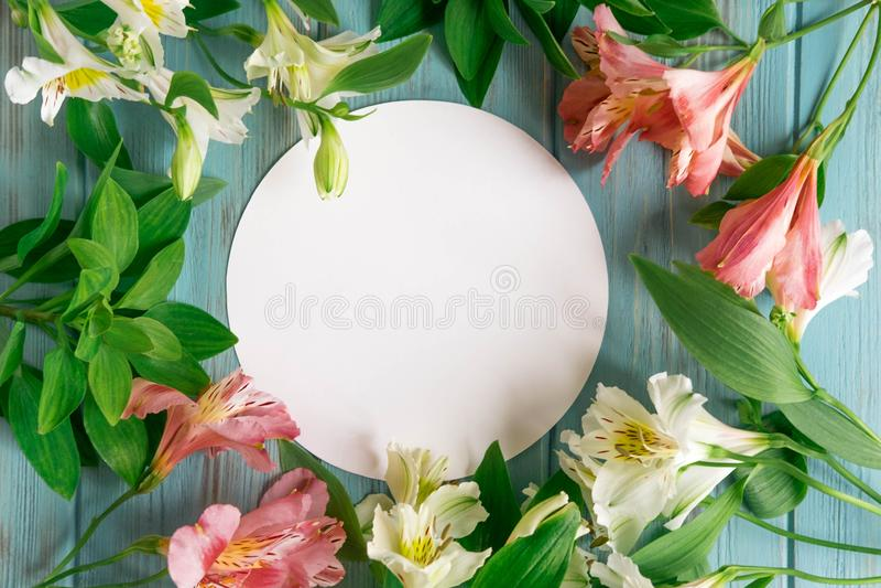 Spott herauf leeres Papier, Postumschlag auf einem blauen hölzernen Hintergrund mit natürlichen weißen und rosa Blumen Freier Rau lizenzfreie stockfotografie