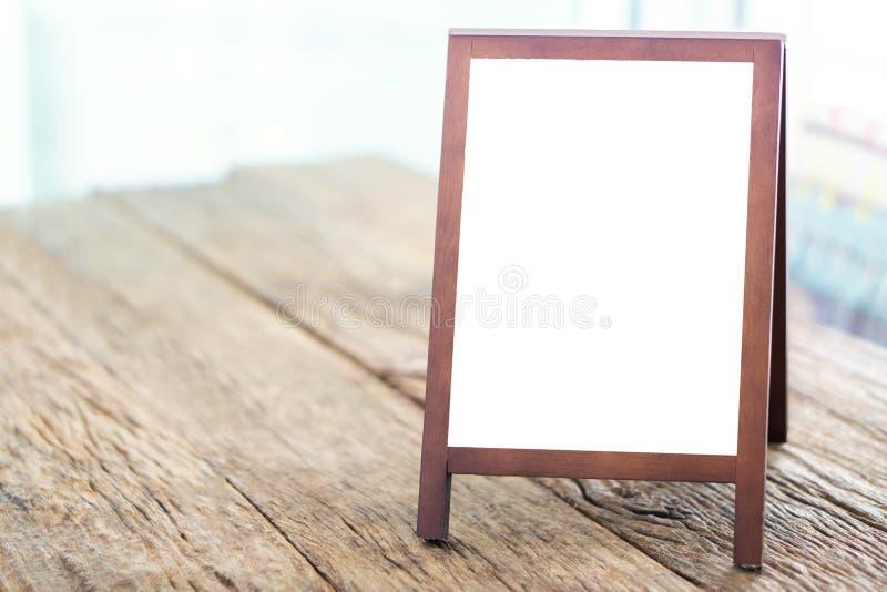 Spott herauf leeres Werbungswhiteboard mit dem Gestell, das auf Holz steht lizenzfreie stockfotografie