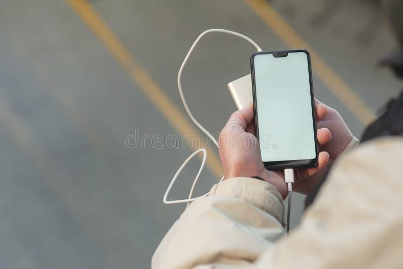 Spott herauf Smartphone mit der tragbaren Aufladung in den Händen eines Mannes stockbild