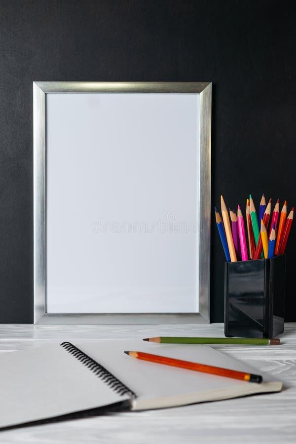 Spott herauf weißen Rahmen und farbige Bleistifte auf hölzernem Regal und Tafel stockfotos