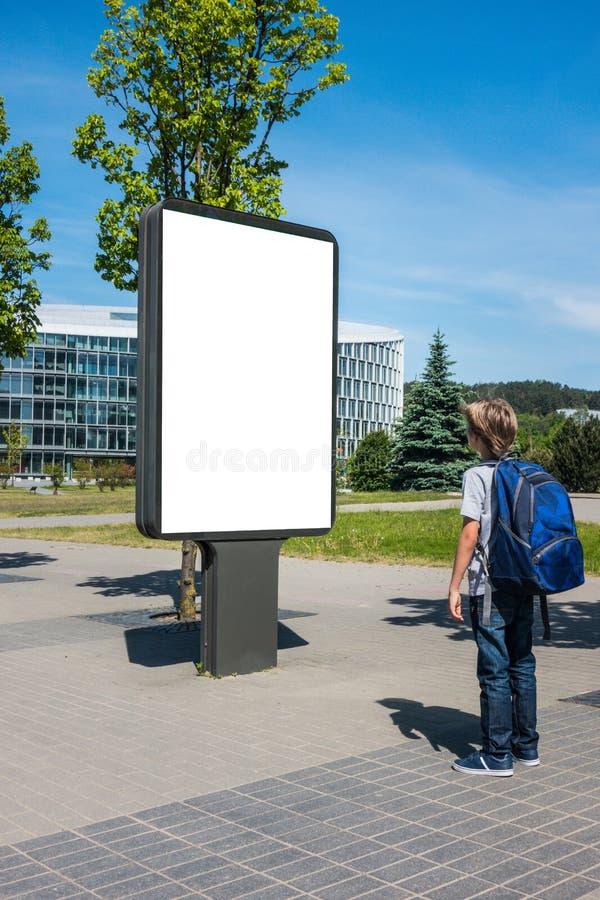 Spott oben Kind, das draußen leere Anschlagtafel, Werbung im Freien, Brett der öffentlichen Information in der Straße betrachtet lizenzfreie stockfotografie