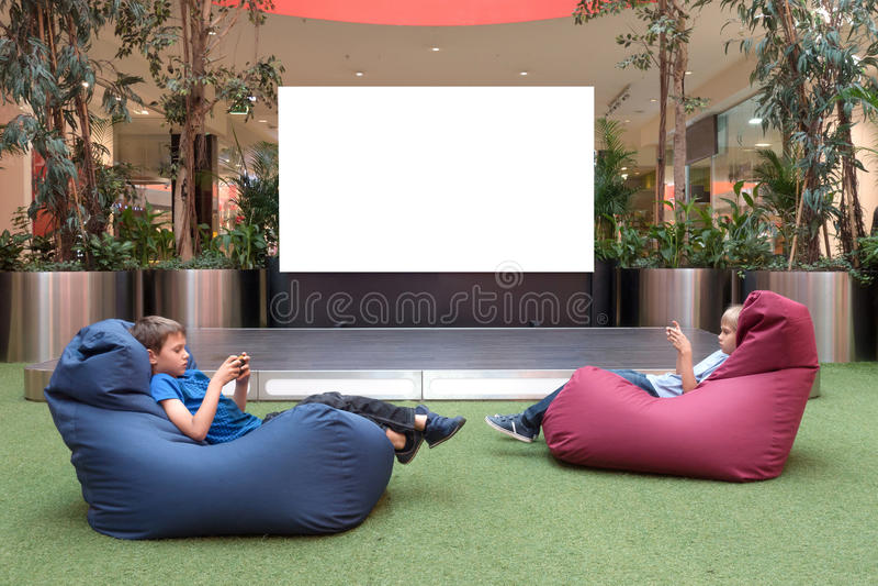 Spott oben Leerer Werbungsschirm im modernen Einkaufszentrum Kinder mit Handy nahe großem leerem digitalem Schirm lizenzfreie stockfotografie