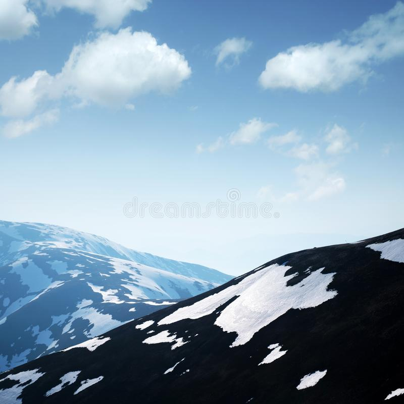 Spotted spring mountains. With snow and grass on clear foggy sky background. Landscape photography stock photo