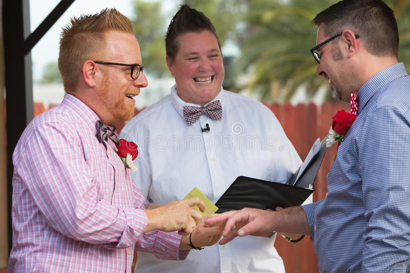 Spouse Puts Ring on Finger. Gay couple in wedding ring ceremony with minister stock photos