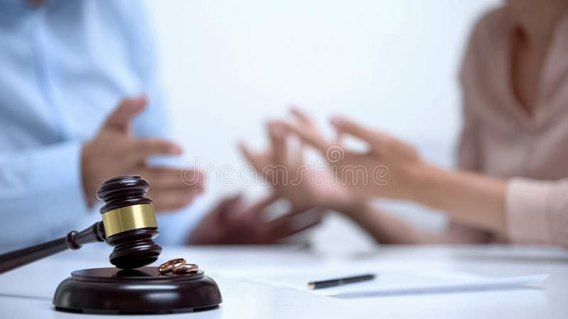 Spouses arguing about property division during divorce, gavel and rings closeup stock images