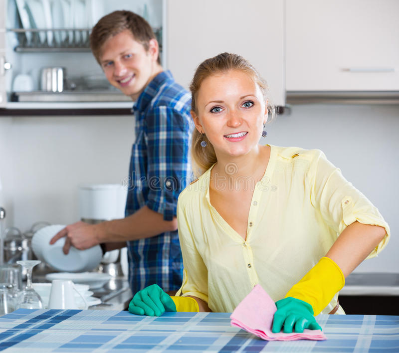 Spouses doing regular housework and polishing. Happy spouses doing regular housework and polishing in kitchen royalty free stock photos
