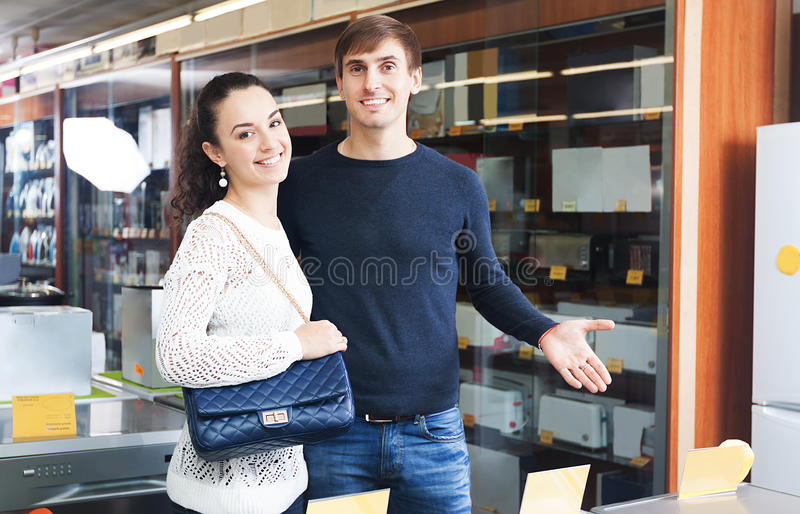 Spouses selecting new domestic appliances. Middle class spouses selecting new domestic appliances at hypermarket stock photography