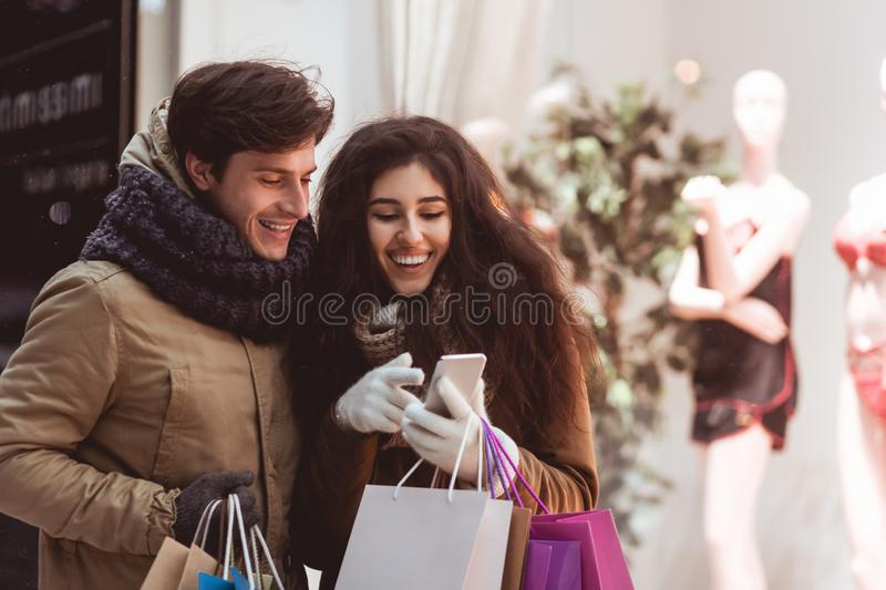 Spouses Using Phone Shopping Walking In City In Winter Evening royalty free stock images
