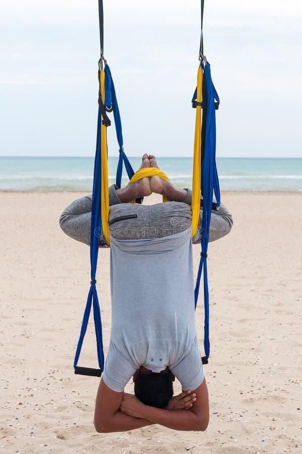 Spoważnienia joga, mężczyzna robi joga ćwiczeniom lub joga na dennym tle fotografia royalty free