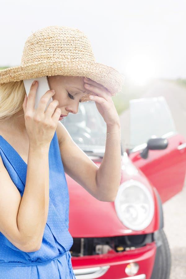 Sprężająca młoda kobieta używa telefon komórkowego łamanym puszka samochodem obrazy stock