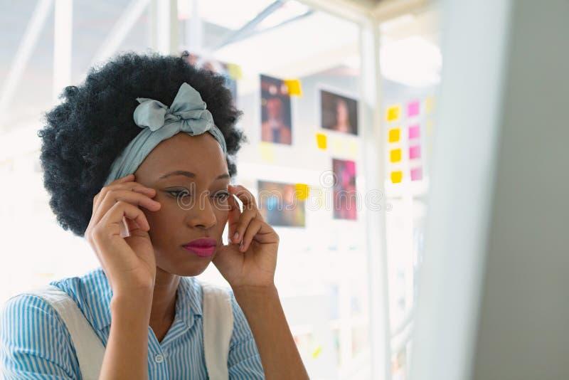 Sprężający żeński projektant grafik komputerowych obsiadanie przy biurkiem obraz royalty free