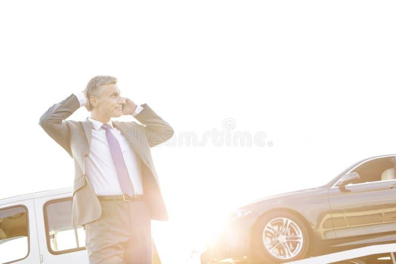 Sprężający biznesmen opowiada na smartphone podczas gdy holownicza ciężarówka podnosi w górę jego samochodu fotografia royalty free