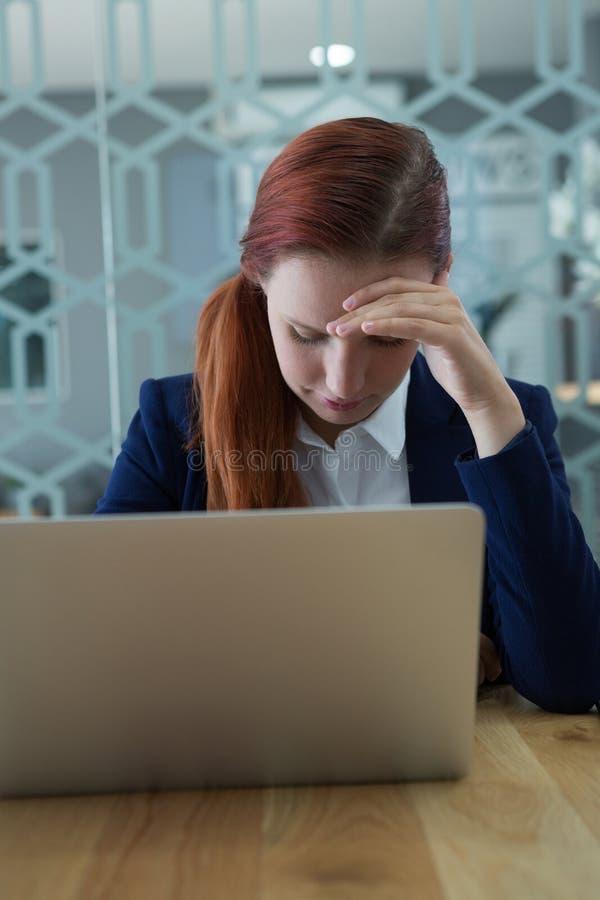 Sprężający bizneswomanu obsiadanie z laptopem przy biurkiem zdjęcie stock