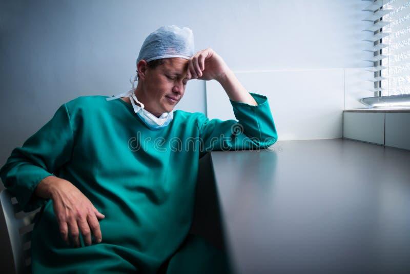 Sprężający męski chirurga obsiadanie przy okno obraz stock