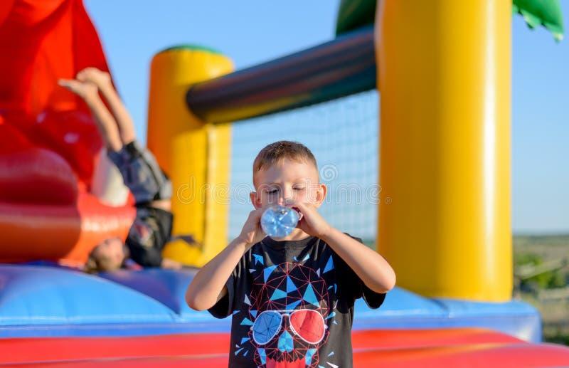 Spragniona młoda chłopiec pije wodę butelkową obraz stock