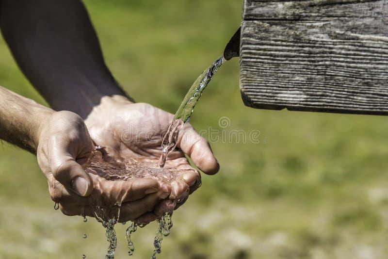Spragnione ręki bierze wodę od well zdjęcia stock