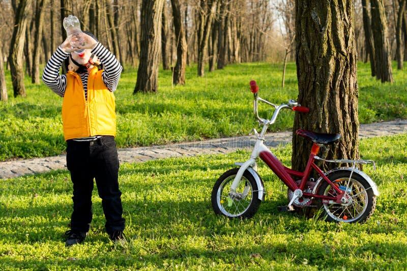Spragniony chłopiec cyklista pije wodę butelkową obrazy stock
