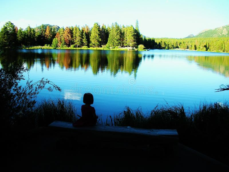 Sprague Lake Rocky Mountain National Park. Young girl sitting on a bench enjoying the view at Sprague Lake Rocky Mountain National Park royalty free stock photo
