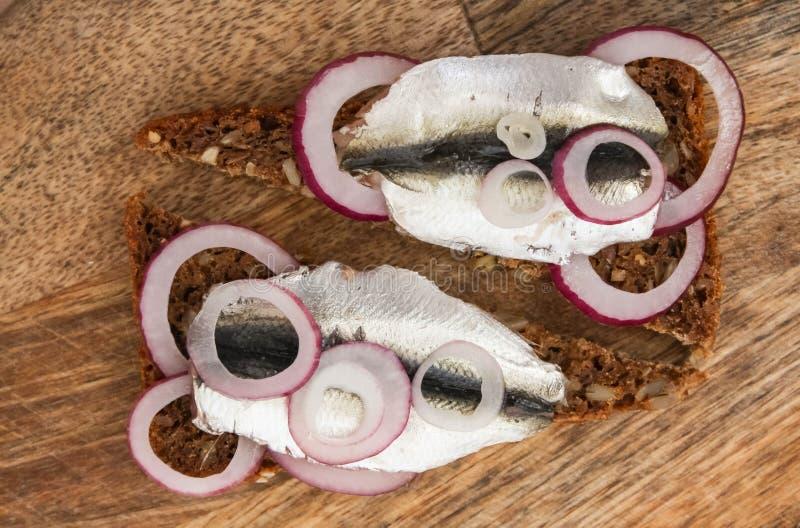 Sprat på ett svart bröd Fisk med bröd och röd lök på ett styckbord fotografering för bildbyråer