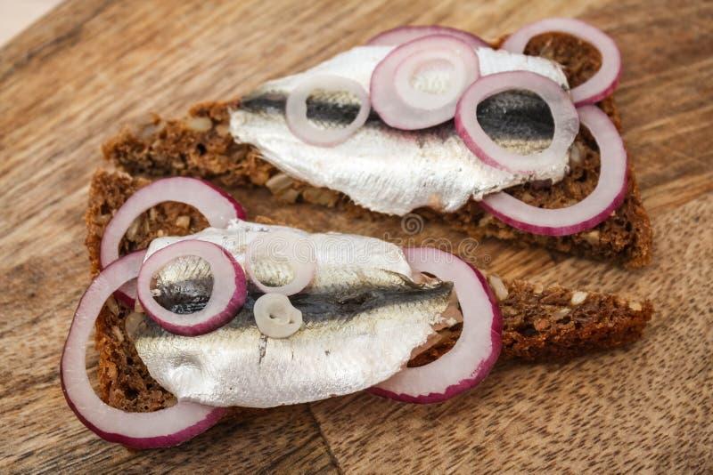 Sprat på ett svart bröd Fisk med bröd och röd lök på ett styckbord arkivfoto