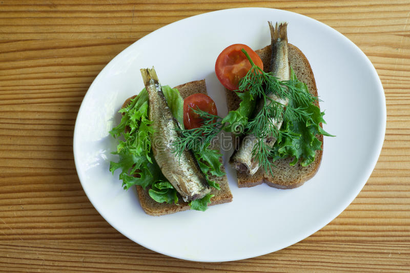 Sprats, bread and tomatoes on a saucer royalty free stock image