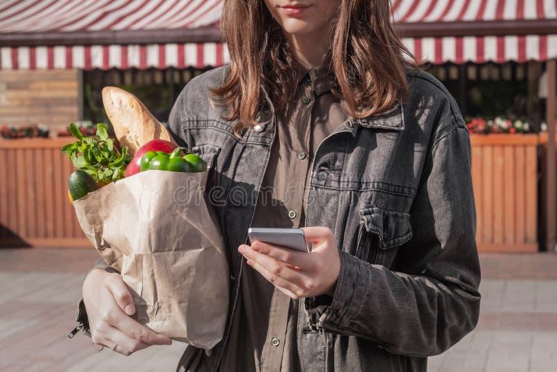 Sprawdzać listę zakupów w smarphone dla jedzenia podczas gdy robiący zakupy Att obrazy royalty free