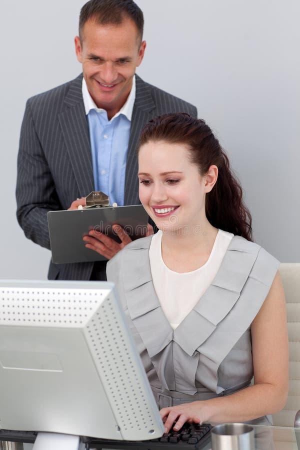 sprawdzać pracownika uśmiechnięta kierownik jego praca s obraz stock