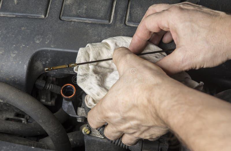 Sprawdza nafcianego poziom przy dipstick oceną w samochodowym silniku obraz stock