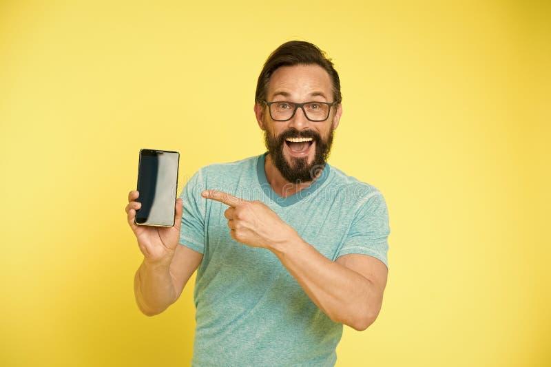 Sprawdza out nowego app Facetów eyeglasses rozochocony wskazywać przy smartphone Mężczyzna szczęśliwy użytkownik poleca próby zas obraz royalty free