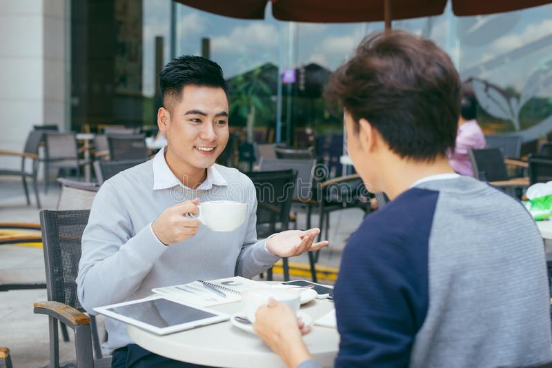 sprawdzanie zapasów Dwa partnera biznesowego pracuje na laptopie ono uśmiecha się radośnie na spotkaniu przy lokalną kawiarnią -  obrazy royalty free
