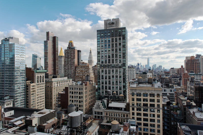 Sprawling Architecture of Midtown Manhattan, NYC. View of Low Rise Rooftops and Skyscrapers in Midtown Manhattan Underneath Blue Sky with White Clouds, New York royalty free stock image